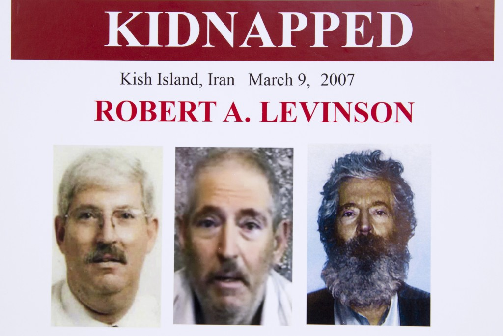 FILE - In this March 6, 2012, file photo, an FBI poster showing a composite image of former FBI agent Robert Levinson, right, of how he would look lik...