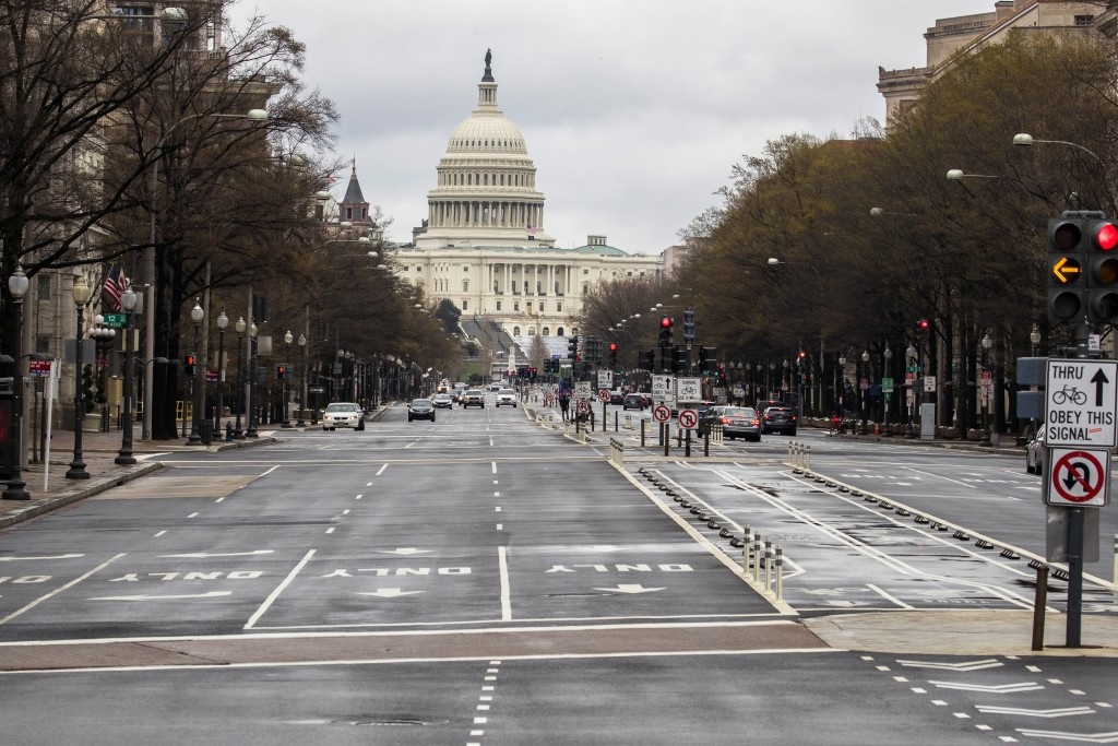 With the U.S. Capitol building in the background, motorists drive on Pennsylvania Avenue NW, Wednesday, March 25, 2020, in Washington. Officials have ...