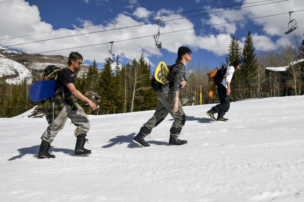 This Tuesday, March 24, 2020 photo shows snowboarders, from left, Colin Tabb, Tyler Alvarez and Shaun Carroll, determined to get in a run, hike up an ...