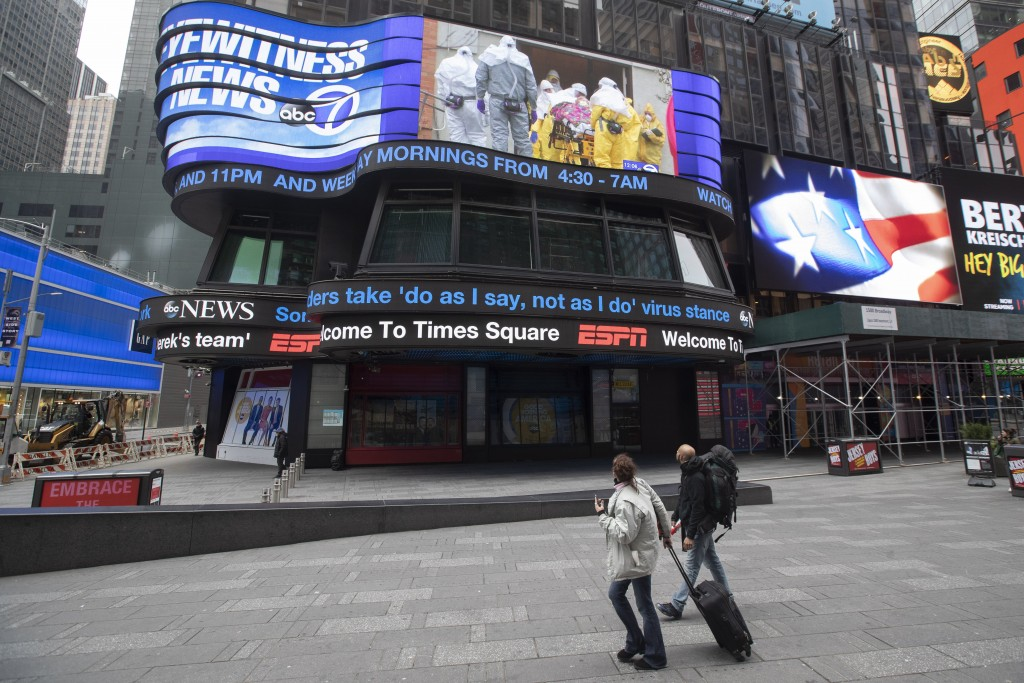 A couple looks at the ABC News video screen showing coverage of a coronavirus outbreak in Woodbridge, N.J., Wednesday, March 25, 2020, in New York's T...
