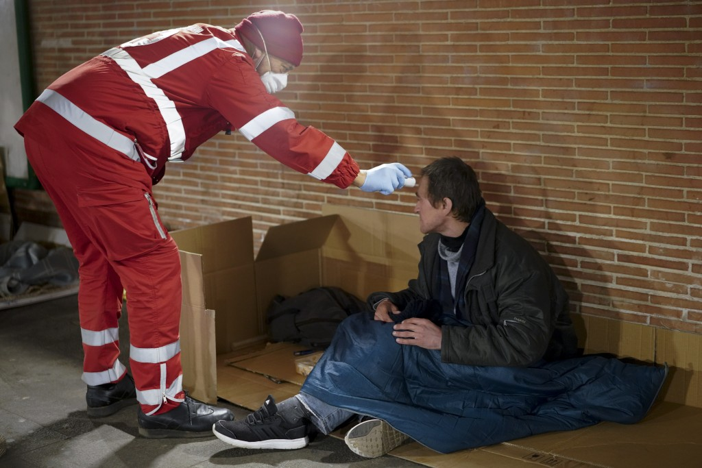 A red cross volunteer checks the temperature of a homeless man, in Rome, Wednesday, March 25, 2020. The new coronavirus causes mild or moderate sympto...
