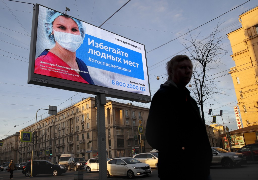"""A man walks past an electronic billboard showing a doctor wearing a medical mask with the words reading """"Avoid crowded places, it will save a life"""", d..."""
