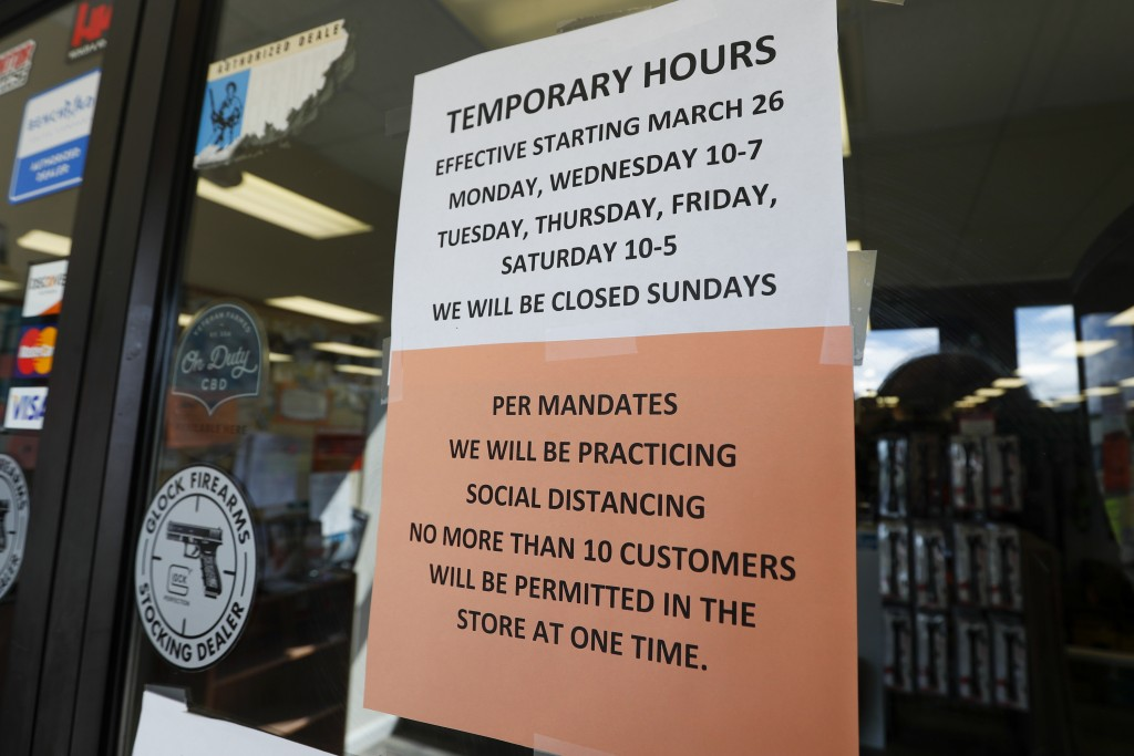 Signs on the front doors of Dukes Sport Shop show the hours and conditions to comply with conditions to reopen Wednesday, March 25, 2020, after being ...