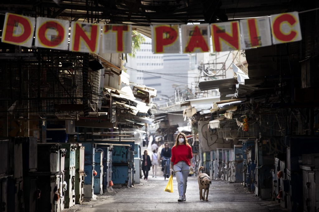 """A woman walks her dog under a """"don't panic"""" sign hanging on the entrance of a food market that was shut down in order to reduce the spread of the coro..."""