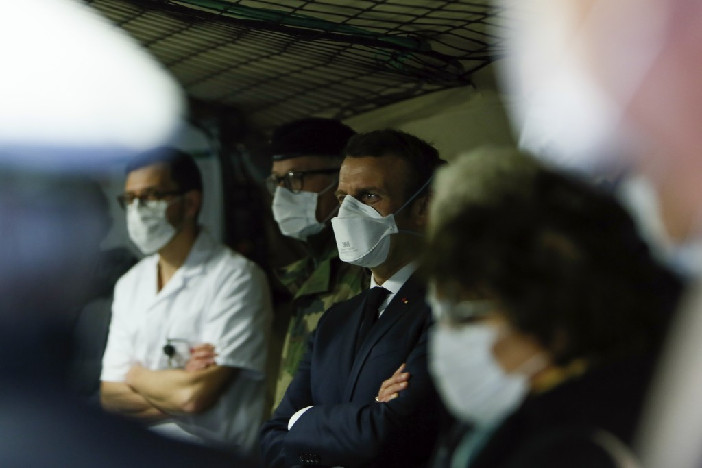 French President Emmanuel Macron, center, wears a face mask as he visits the military field hospital in Mulhouse, eastern France, Wednesday, March 25,...