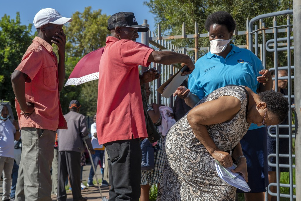 People seeking medical assistance queue outside a local clinic in the township of Soweto, near Johannesburg, South Africa, Thursday March 26, 2020, ju...