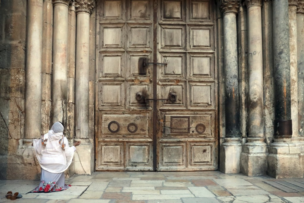 A woman prays in front of the closed Church of the Holy Sepulchre, a place where Christians believe Jesus Christ was buried, in Jerusalem, Wednesday, ...