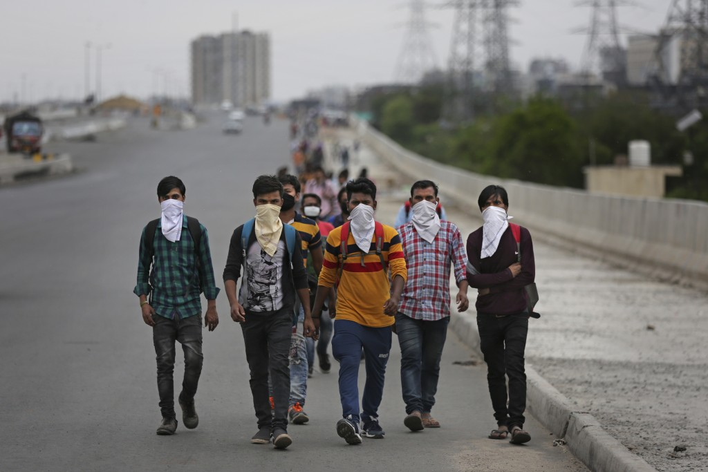 A group of Indian daily wage laborers walk along an expressway hoping to reach their homes, hundreds of kilometers away, as the city comes under lockd...