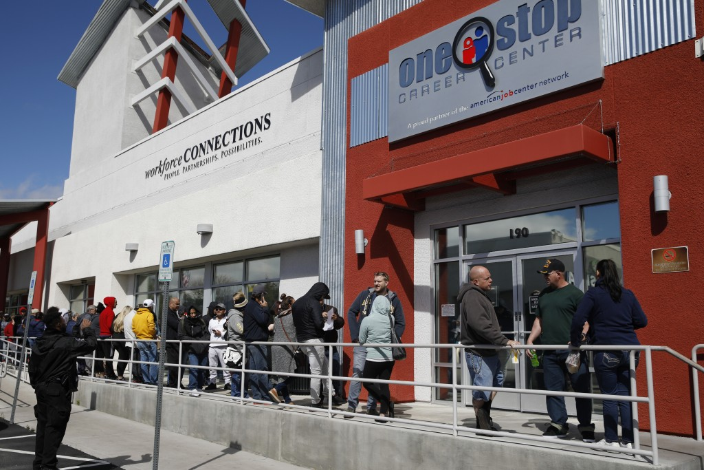 FILE - In this March 17, 2020 file photo, people wait in line for help with unemployment benefits at the One-Stop Career Center in Las Vegas.   A reco...