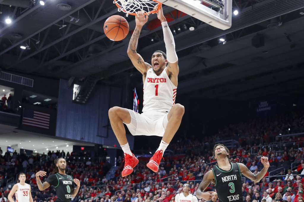FILE - In this Dec. 17, 2019, file photo, Dayton's Obi Toppin (1) dunks as North Texas' Javion Hamlet (3) looks on during the second half of an NCAA c...