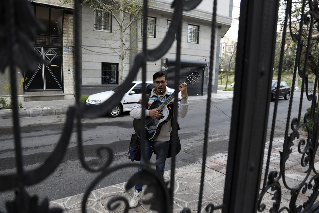 A street musician sings and plays music on an empty lane in Tehran, Iran, Thursday, March 26, 2020. Iran is battling the worst new coronavirus outbrea...