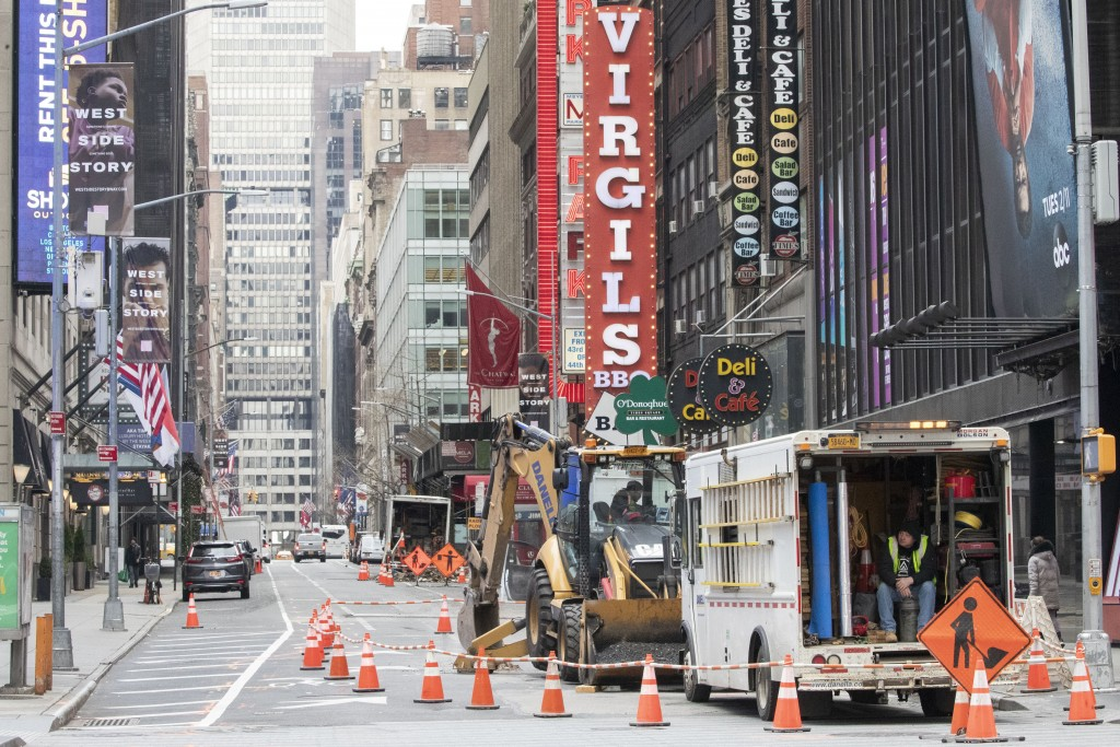Construction workers are seen an an empty street, Wednesday, March 25, 2020, in New York's Times Square. The number of people hospitalized with COVID-...