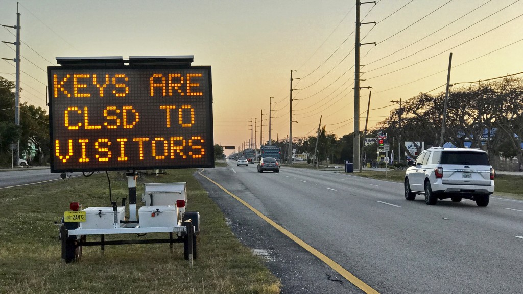 In this photo provided by the Florida Keys News Bureau, cars pass an electronic messaging board on the Florida Keys Overseas Highway, Wednesday, March...