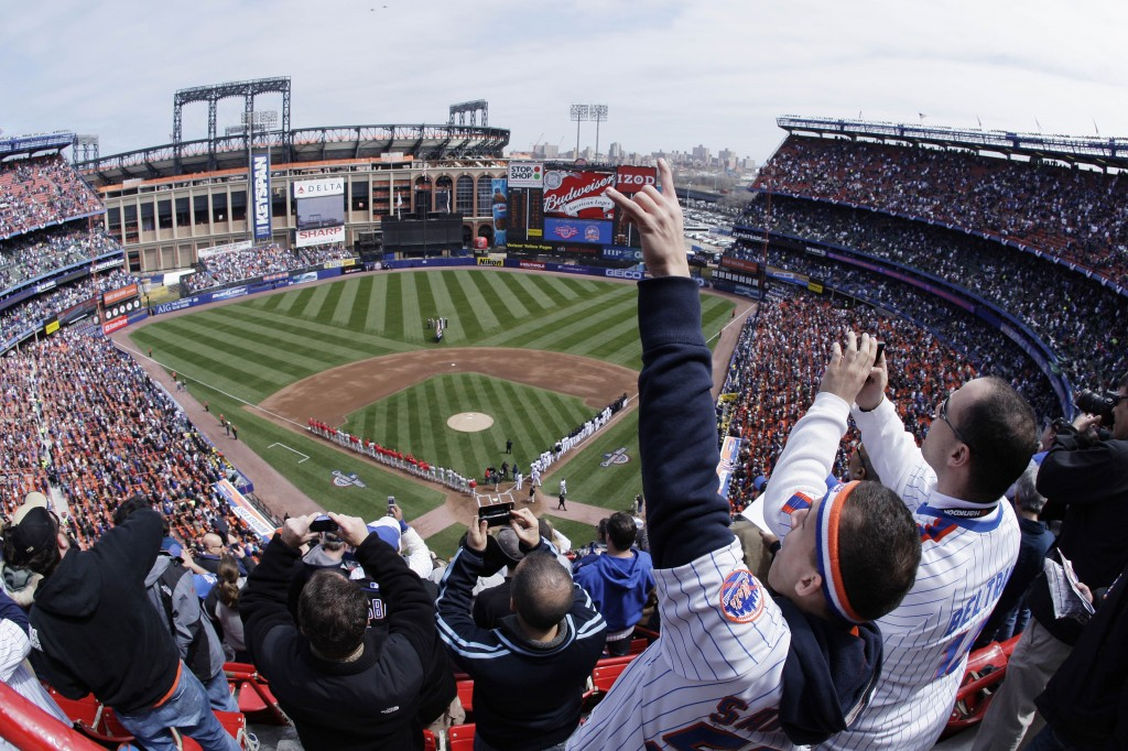 FILE - In this April 8, 2008, file photo, New York Mets fans look skyward for a fly-over at the end of the national anthem before an opening day baseb...