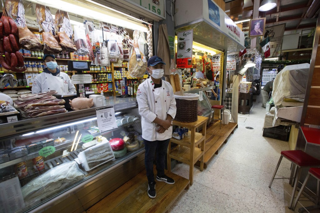 Vendors wearing protective face masks wait for shoppers at the popular San Juan food market in Mexico City, Wednesday, March 25, 2020. Mexico's capita...
