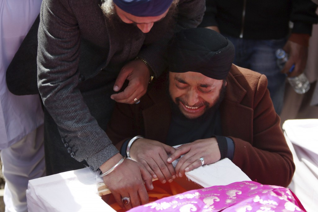 Afghan Sikh men mourn their beloved ones during a funeral procession for those who were killed on Wednesday by a lone Islamic State gunman, rampaged t...