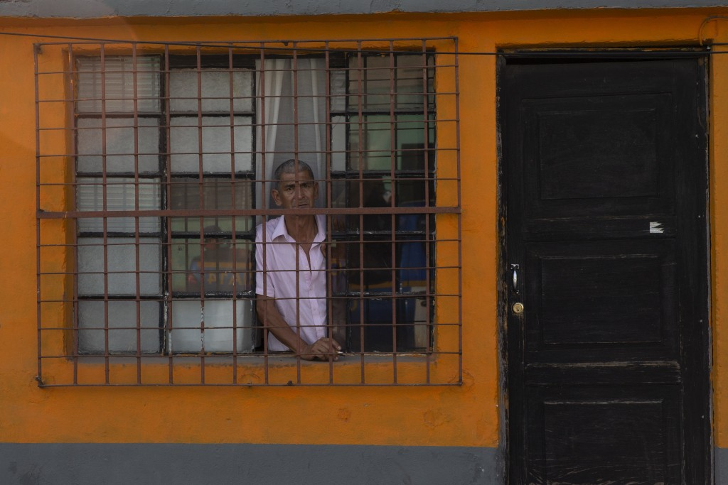 A neighbor watches from his house as police patrol during the fourth day of a curfew to help prevent the spread of the new coronavirus in Villa Nueva,...