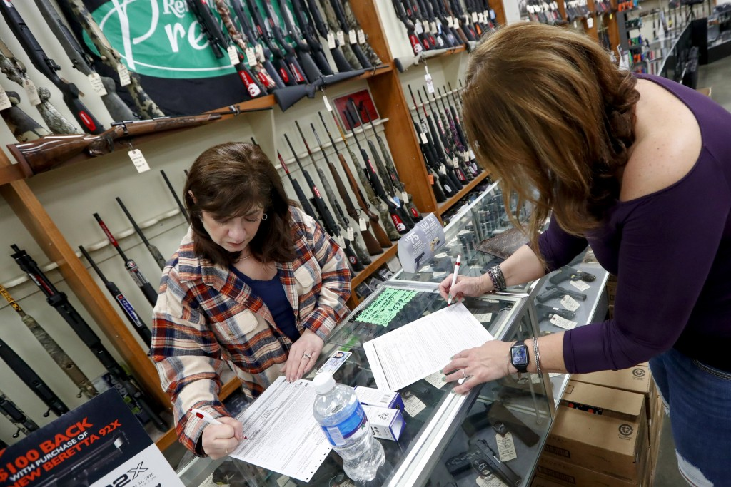 Andrea Schry, right, fills out the buyer part of legal forms to buy a handgun as shop worker Missy Morosky fills out the vendors parts after Dukes Spo...