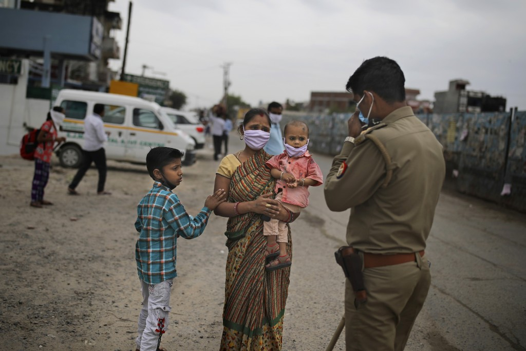 An Indian woman pleads in front of a policeman to let her pass a check point hoping to walk to their home with her family, a few hundred kilometers aw...