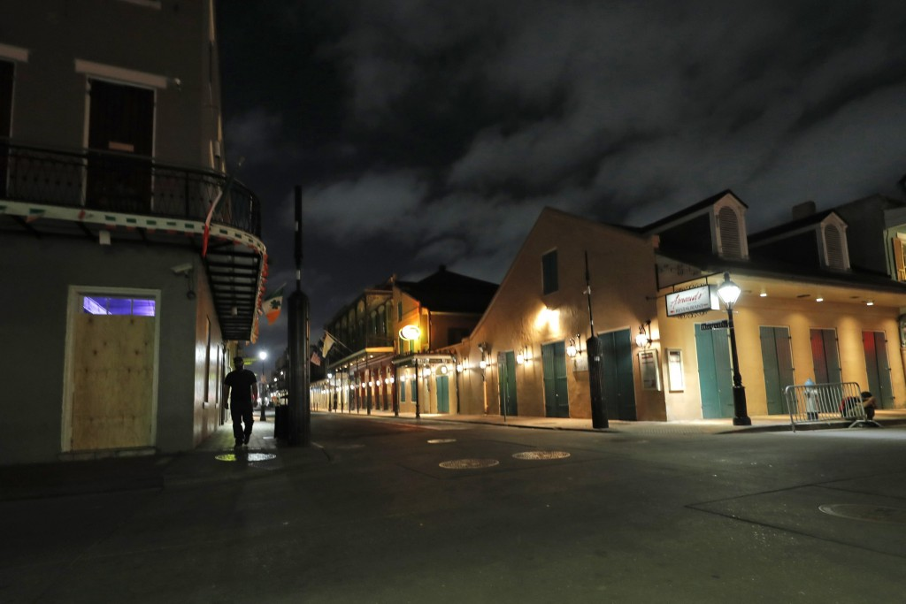 FILE - In this Thursday, March 19, 2020, file photo, a view of the nearly deserted Bourbon Street, which is normally bustling with tourists and revele...