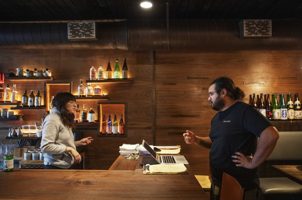 James Mark, right, owner of the restaurant Big King, talks with Jennifer Wittlin as they prepare for dinner take-out orders Wednesday, March 25, 2020,...