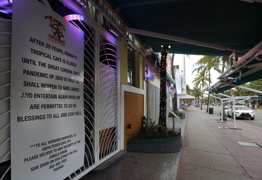 A sign is shown outside the closed Mango's Tropical Cafe along the normally bustling streets of the Art Deco district, Wednesday, March 25, 2020, in M...