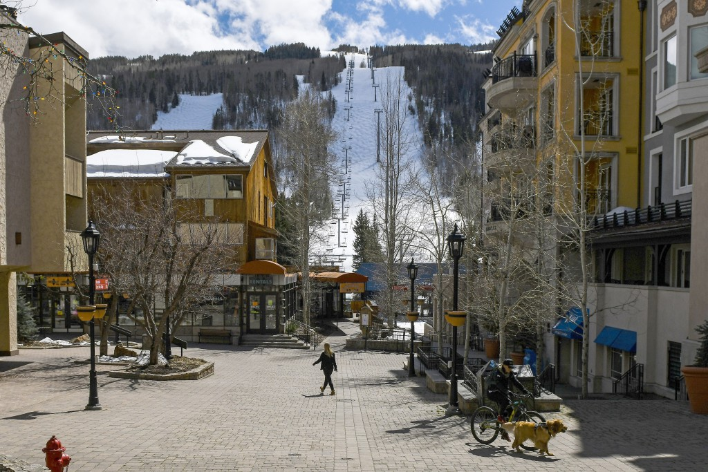 This Tuesday, March 24, 2020 photo shows people walking through empty streets at the base of Vail Ski Resort after the resort closed for the season am...