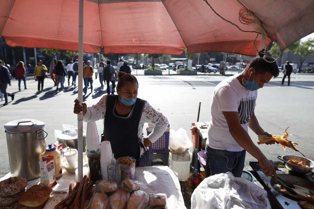 Lourdes Sanvicente, 45, left, and a coworker wear protective face masks at the direction of the stand's owner, as they sell tamales, sandwiches, and p...