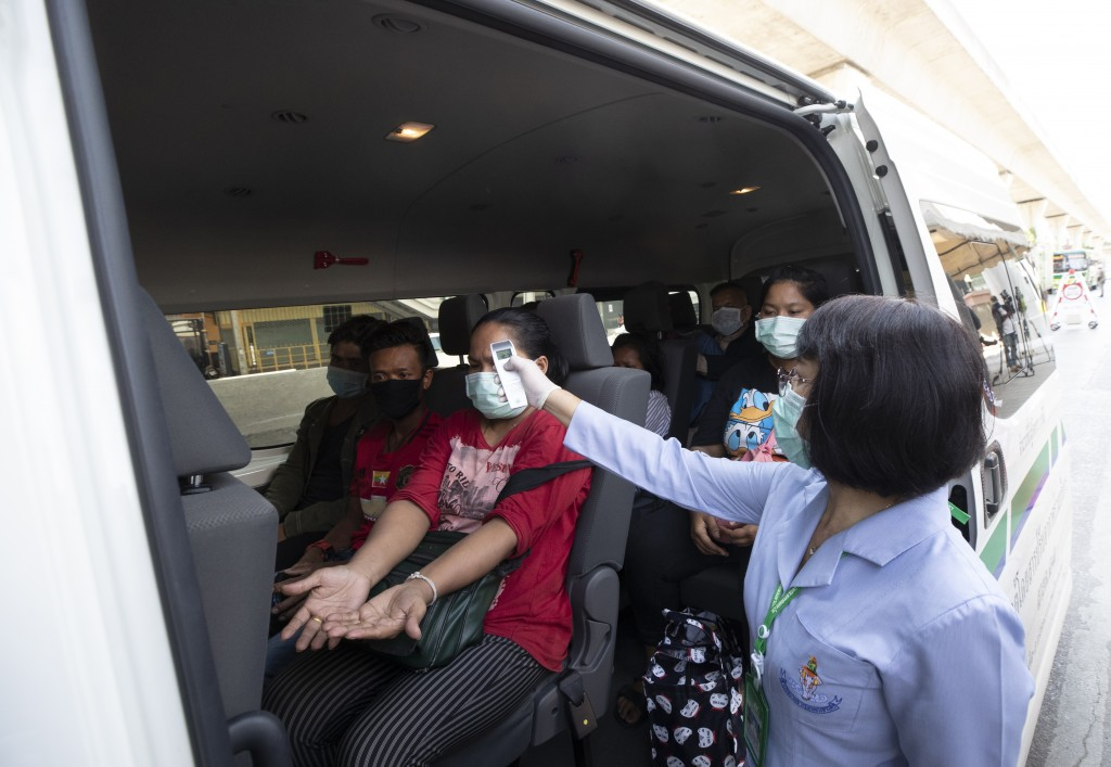 Health officer check temperature passenger in van at a health check point in Bangkok, Thailand, Thursday, March 26, 2020. It is the first day of month...