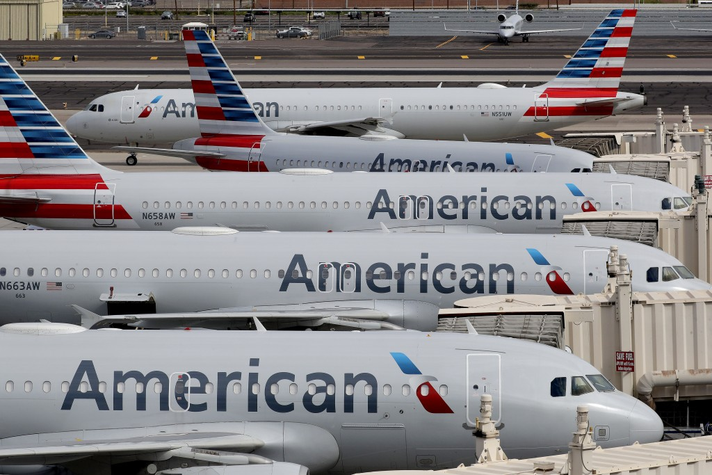 FILE - In this Wednesday, March 25, 2020 file photo, American Airlines jets sit idly at their gates as a jet arrives at Sky Harbor International Airpo...