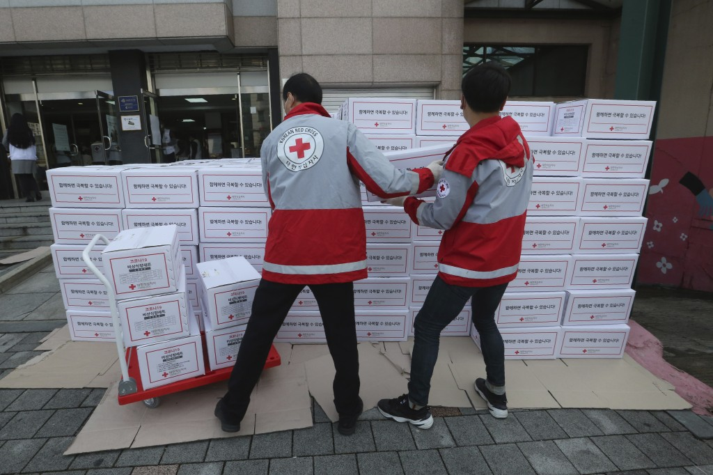 Red Cross workers carry boxes containing emergency relief kits packed with basic necessities like instant food for delivery to impoverished people exp...