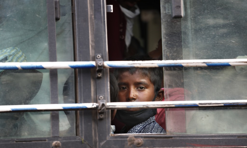 The son of a migrant daily wage laborer looks out a bus window bus as he travels to his hometown following a lockdown amid concern over spread of coro...