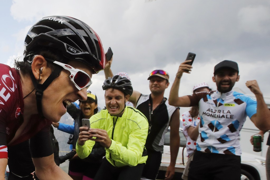 FILE - In this file photo taken on July 25, 2019 spectators cheer Britain's Geraint Thomas climbing the Galibier pass during the eighteenth stage of t...