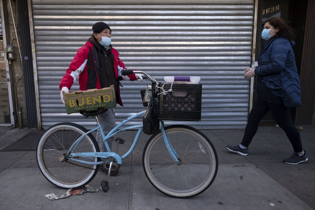 A man balances boxes of food that he picked up from Masbia Soup Kitchen, Thursday, March 26, 2020 during the coronavirus pandemic in the Brooklyn boro...