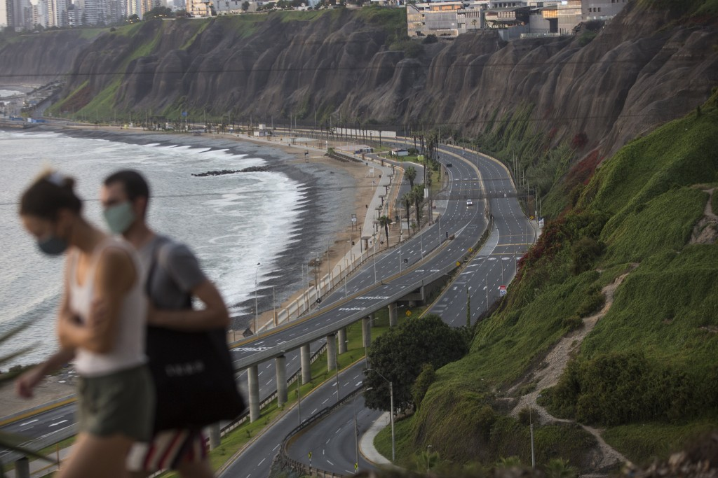 With an empty highway in the background, Liza Mell, 26, and Jean-Marie Landre, 27, both French citizens living in Lima, Peru, walk wearing a protectiv...