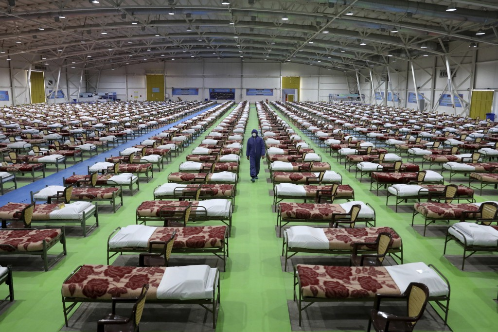 A member of the Iranian army walks past rows of beds at a temporary 2,000-bed hospital for COVID-19 coronavirus patients set up by the army at the int...