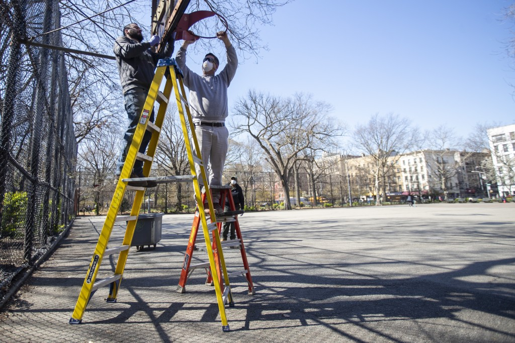 New York City Department of Parks and Recreation employees remove the basketball hoop from a court in Tompkins Square Park, Thursday, March 26, 2020, ...