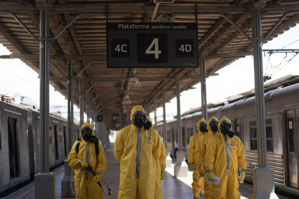 Soldiers stand in formation before disinfecting wagons for the new coronavirus at the central train station in Rio de Janeiro, Brazil, where trains co...