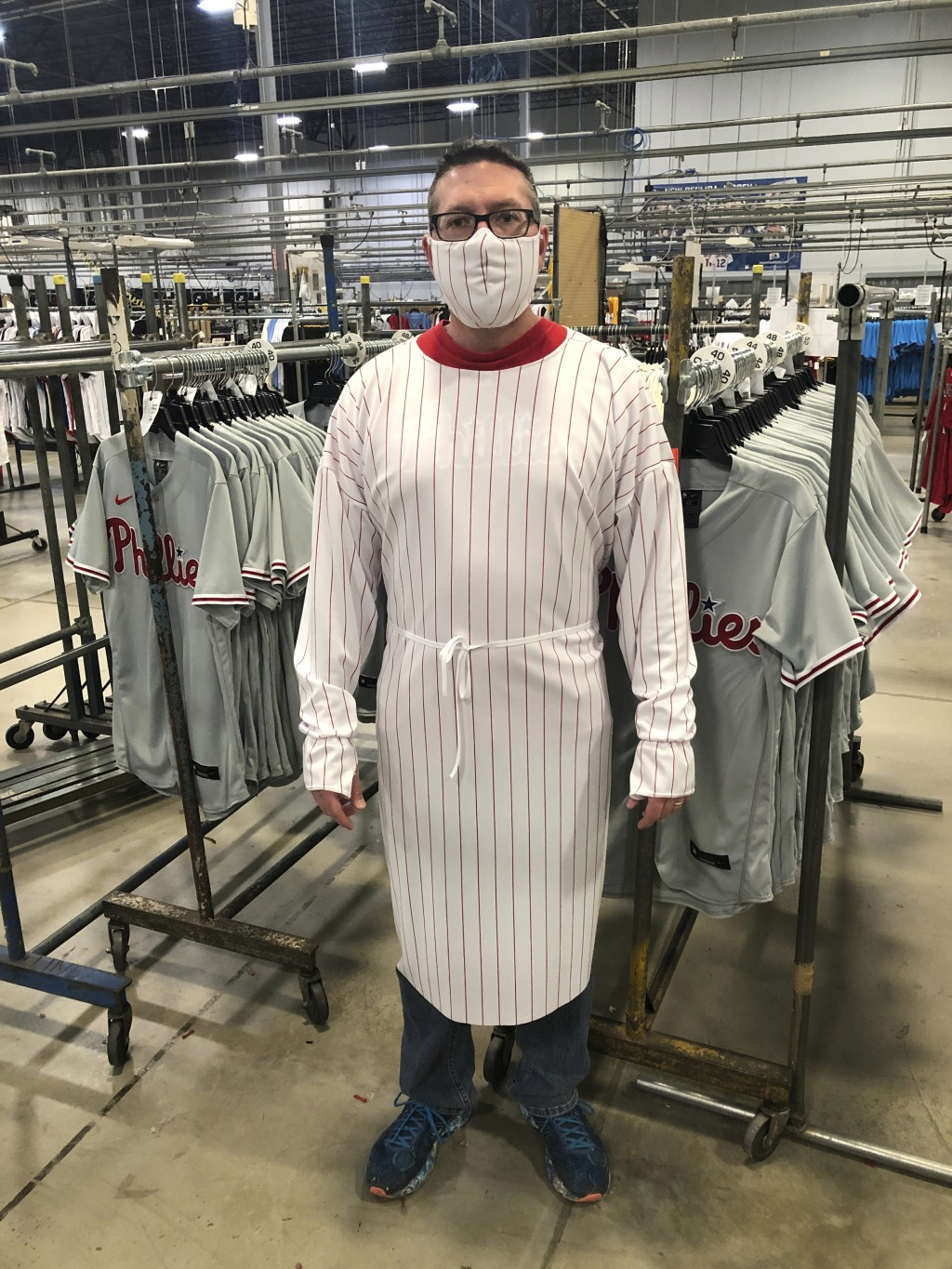 This image provided by Fanatics, shows a model wearing a protective mask and gown for medical professionals made from the fabric of a baseball uniform...