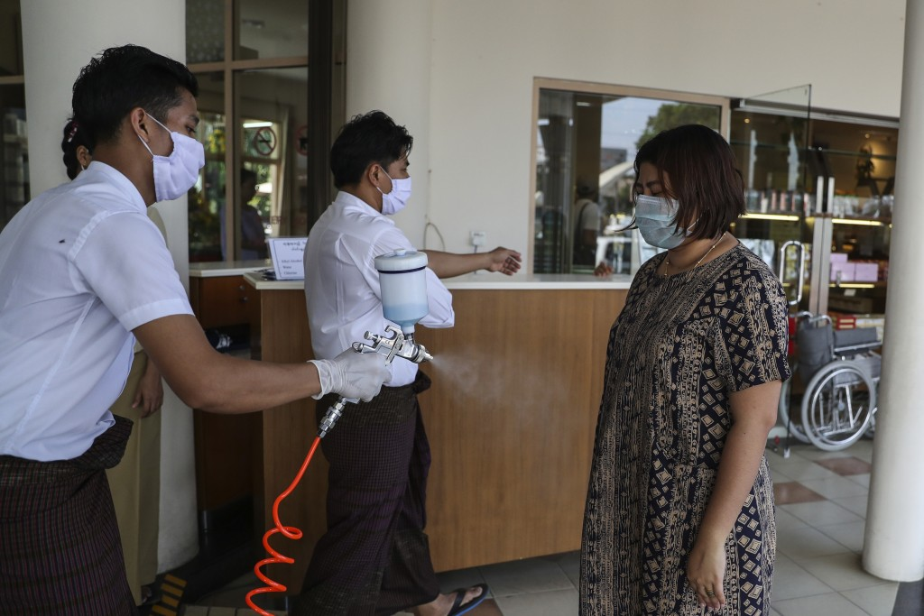 A staff member sprays disinfectant to a customer at the entrance of a cafeteria shop in Yangon, Myanmar Friday, March 27, 2020. The new coronavirus ca...