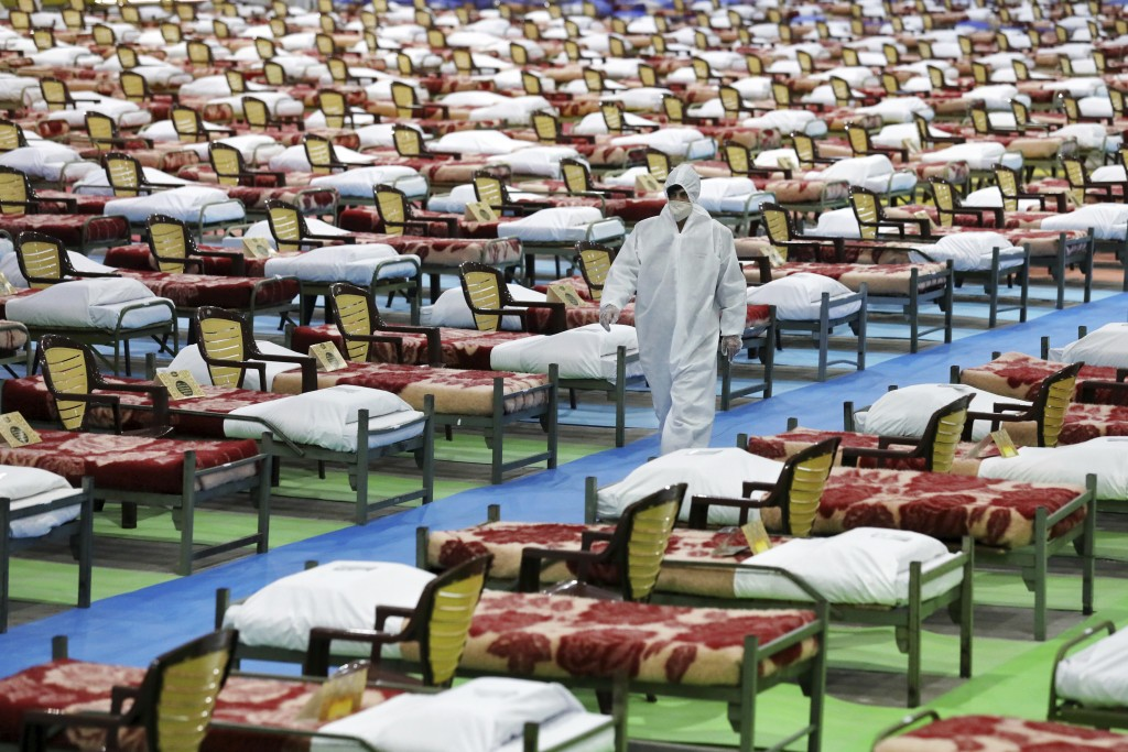 A person in protective clothing walks through a temporary 2,000-bed hospital for COVID-19 coronavirus patients set up by the Iranian army at the inter...