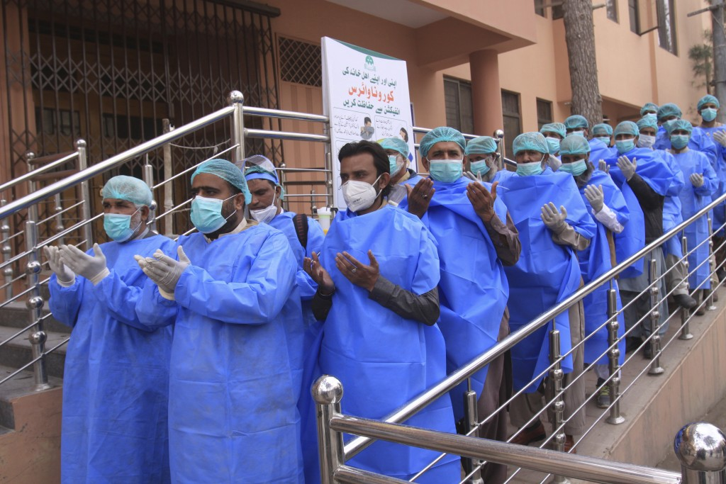 Hospital staff pray before joining their shift, outside a hospital setup for coronavirus infected patients in Quetta, Pakistan, Thursday, March 26, 20...