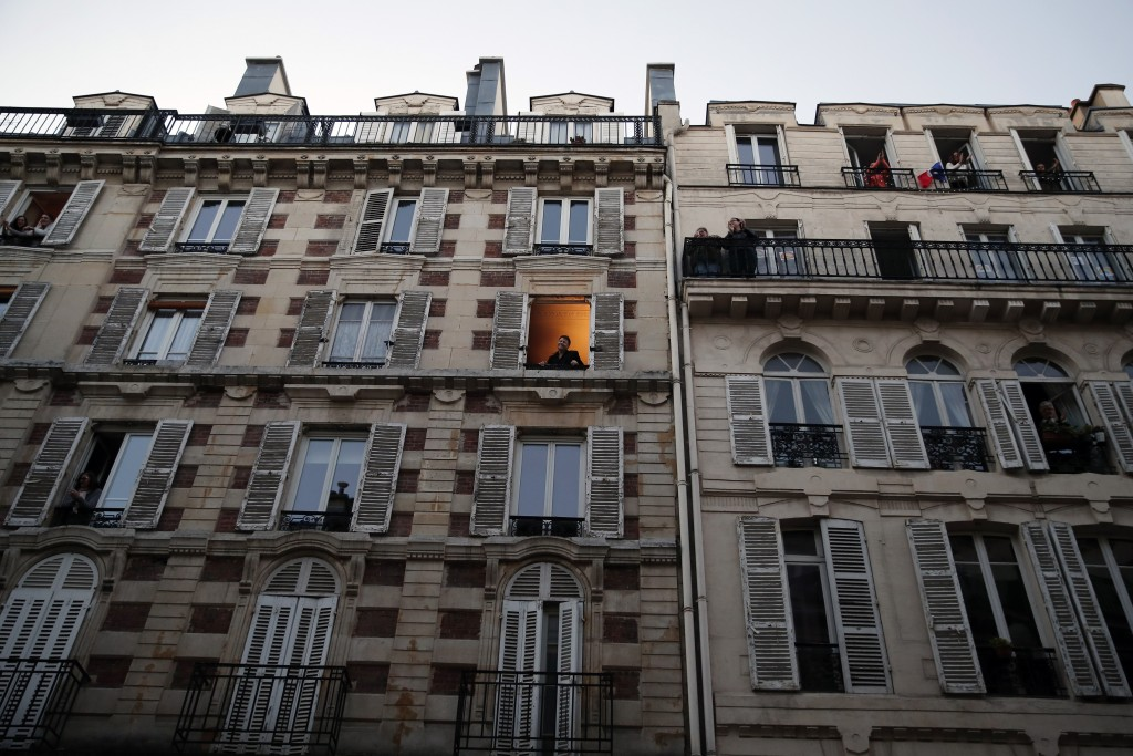 Tenor Stephane Senechal, center, acknowledges applause after singing from his apartment window in Paris, Tuesday, March 24, 2020. President Emmanuel M...