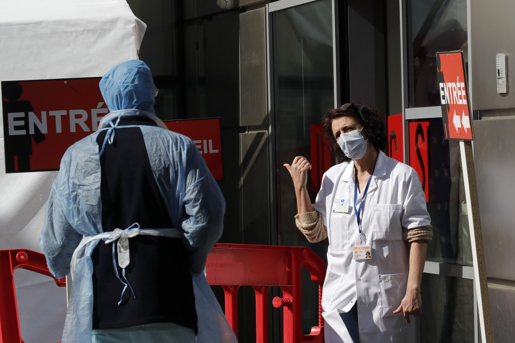 Doctors speak outside a tent used as a waiting room for people with COVID-19 symptoms at the Tenon hospital in Paris on Thursday, March 26, 2020. (AP ...