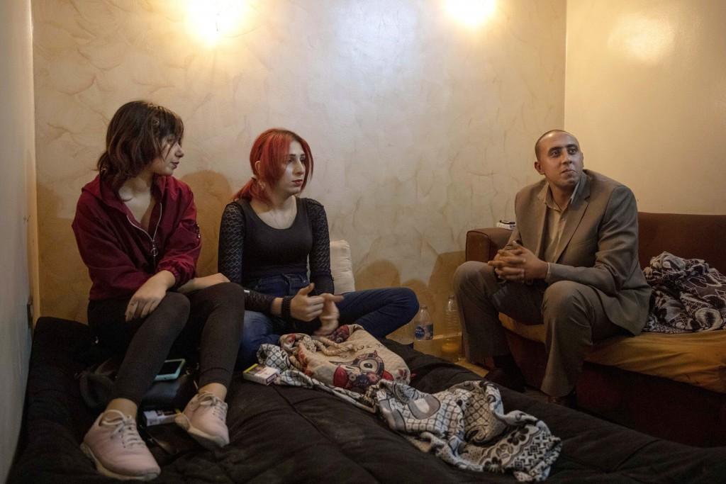 In this Oct. 28, 2019 photo, activist and transgender woman Malak el-Kashif, center, sits with her lawyer and friend at her apartment in Cairo, Egypt....