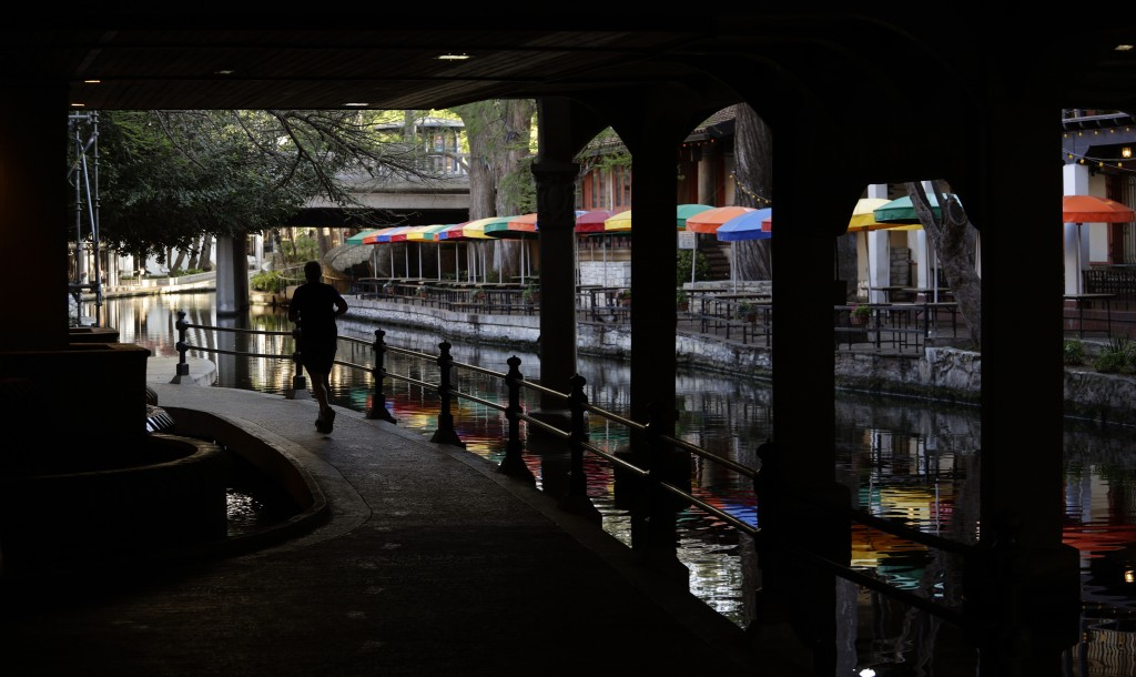 FILE - In this March 24, 2020, file photo, a runner moves along a mostly deserted River Walk in San Antonio, where most restaurants and business are c...