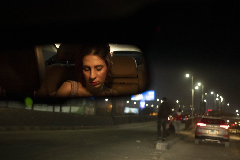 In this Feb. 20, 2020 photo, transgender woman and activist Malak el-Kashif, reflected in the rear view mirror of a car, looks at her mobile phone, in...