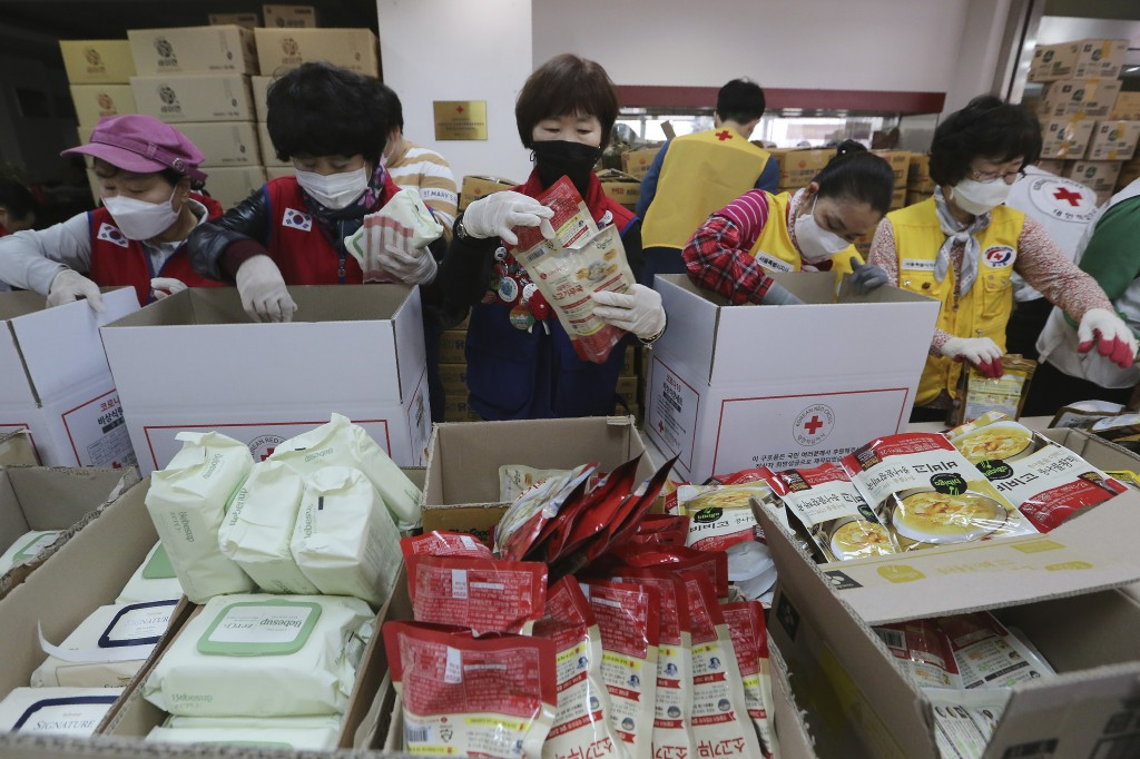 Red Cross workers prepare emergency relief kits packed with basic necessities including instant food for delivery to impoverished people experiencing ...