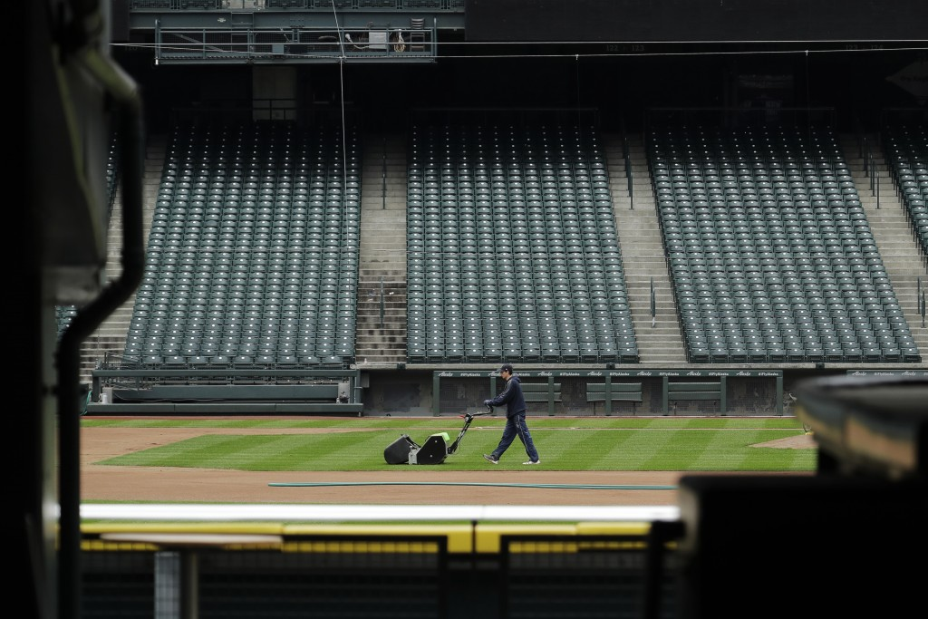 A grounds crew worker cuts the infield in front of empty seats at T-Mobile Park in Seattle, March 26, 2020, around the time when the first pitch would...