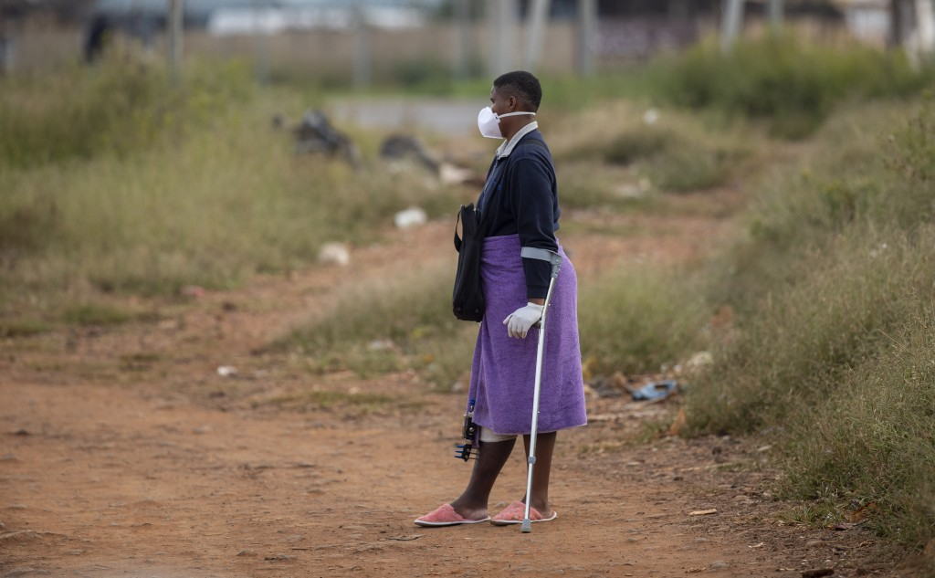 Noxolo Mbatha, wearing face masks and surgical gloves to protect herself against coronavirus, awaits a taxi for her hospital appointment at a informal...